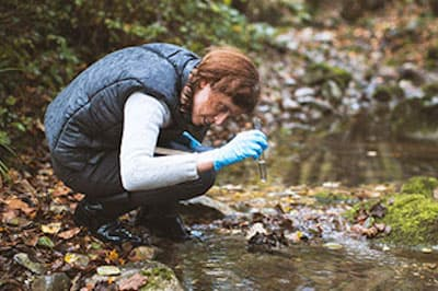 Woman take vial of water from creek