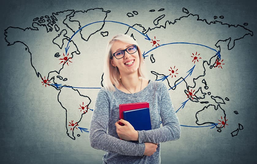 Female in front of world map holding books
