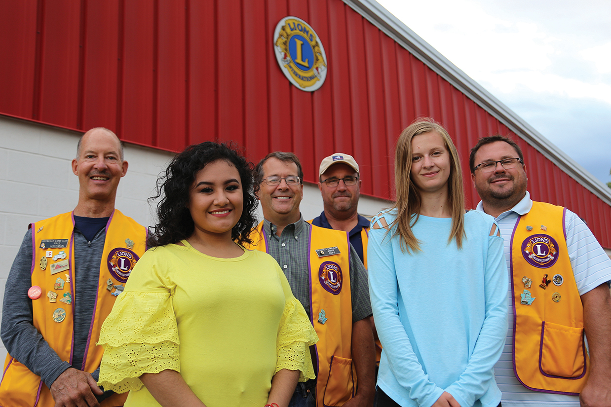 Scholarship recipients Fatima Leon Cuevas (left) and Erin Goodson with members of the Greenville Lions Club
